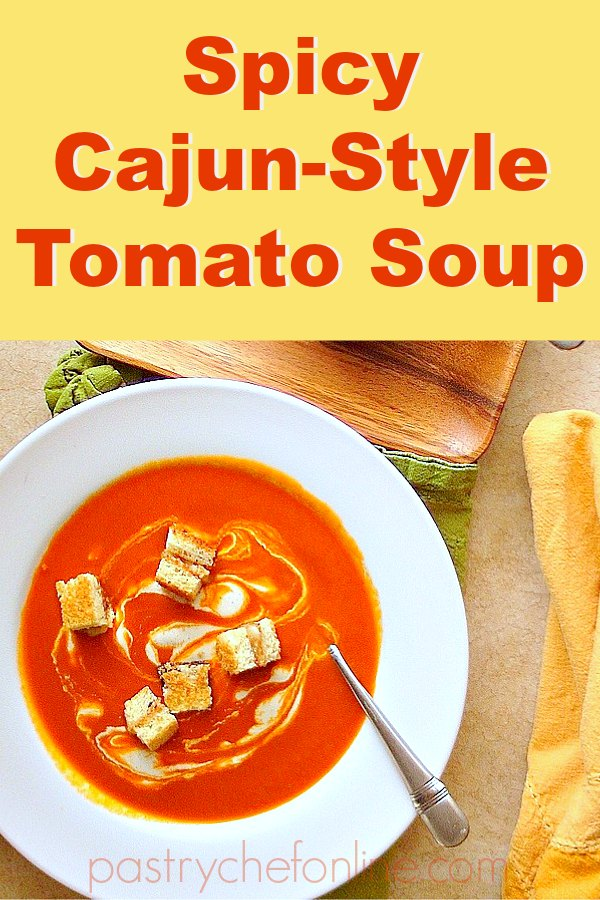 """pin image for cajun spicy tomato soup bowl of soup with croutons. text reachs """"spicy cajun-style tomato soup:"""