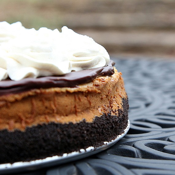 partial shot of side of cheesecake with Oreo crust and whipped cream