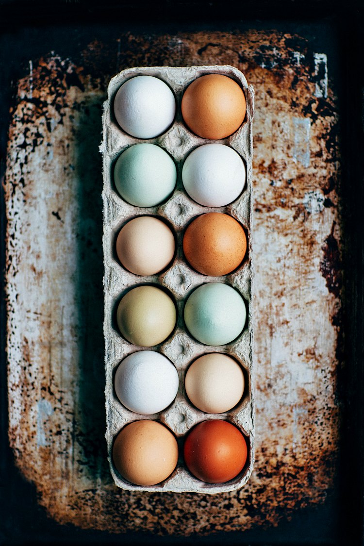 An overhead shot of a dozen different colored eggs in a carton on a distressed background.