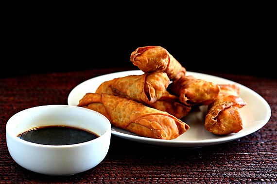 Fried pork appetizers with dipping sauce on a plate.