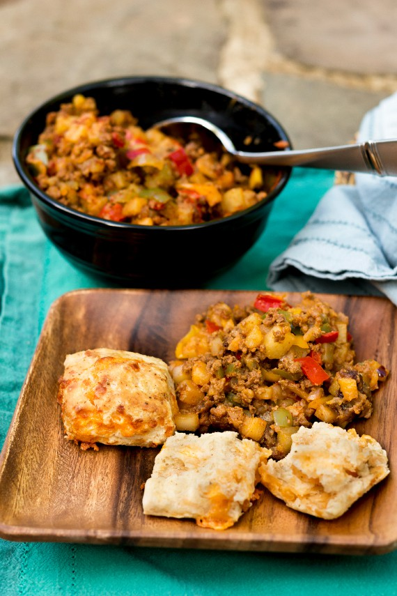 high-rise flaky cheddar biscuits on a wooden plate with chili