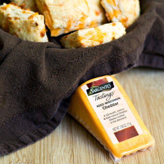 a basket of cheese biscuits and a wedge of cheddar cheese