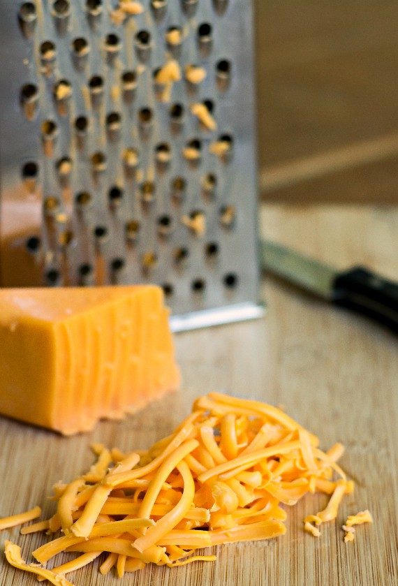 a grater, a block of cheese, and some shredded cheese on a cutting board
