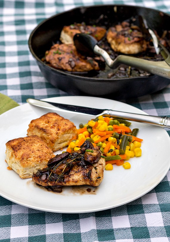 Chicken thigh with mushrooms and thyme, 2 biscuits, and mixed vegetables on a white plate with a cast iron skillet in the background with more thighs.