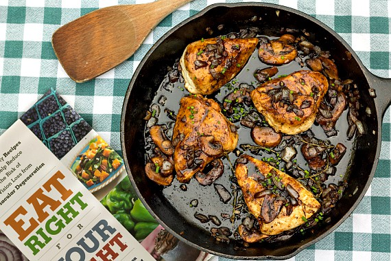 Overhead shot of the Eat Right for Your Sight cookbook and a cast iron skillet with 4 chicken thighs.