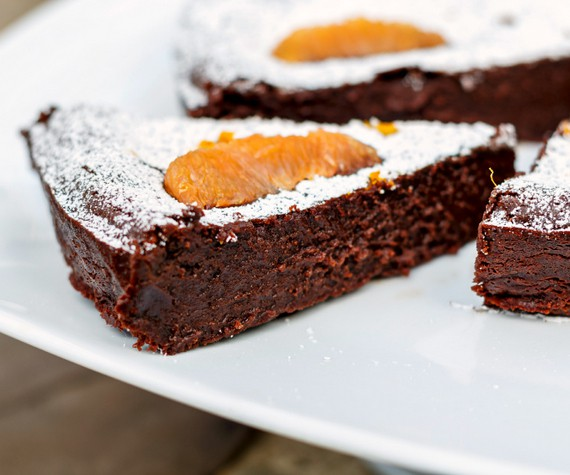 a fudgy slice of gluten free chocolate cake with an orange slice on it