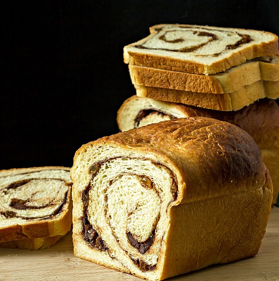 a sliced loaf of cinnamon raisin swirl bread with stacked up slices