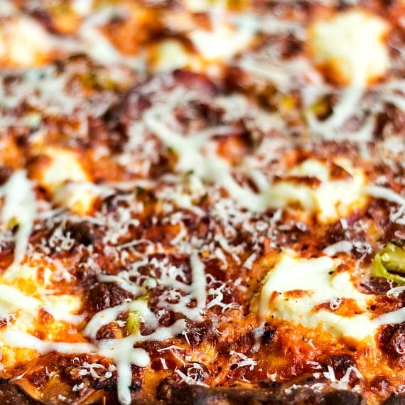 Close up view of a baked pizza with cheese and vodka sauce.