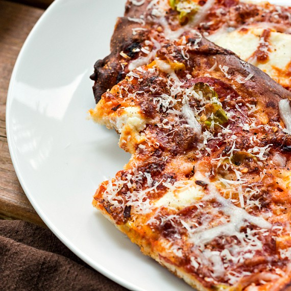 A close up of a slice of pizza with a bite taken out of it.