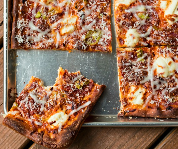 A baked grandma pizza recipe made with vodka sauce and topped with cheese and pepperoncini on a baking sheet. One piece has been cut  and is being served.