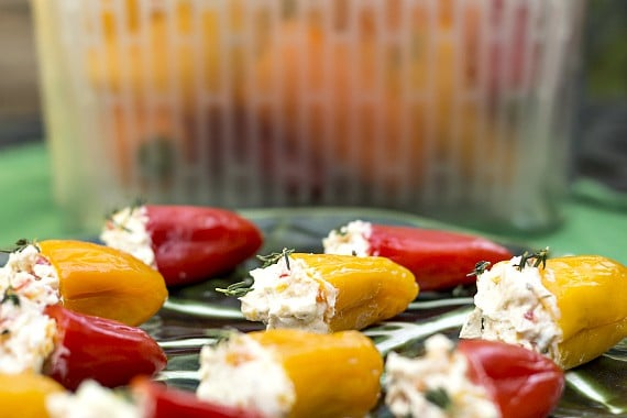Red, yellow, and orange mini peppers stuffed with agoat cheese filling on a green plate.