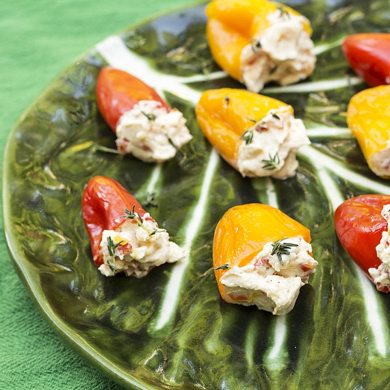 Tangy Pickled Peppers Stuffed with Herbed Goat Cheese on a green cabbage leaf design glass platter.