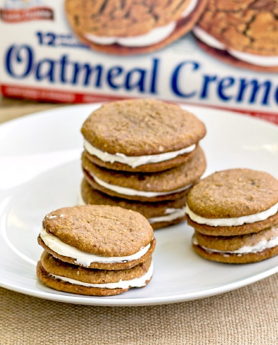Oatmeal cream pie sandwich cookies stacked on a white plate with a box of Little Debbie oatmeal Creme Pies in the background.