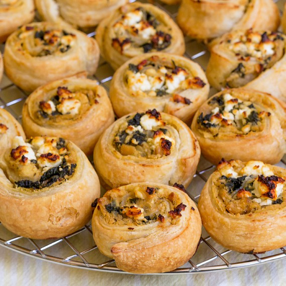 close up of hummus puff pastry pinwheels cooling on a rack