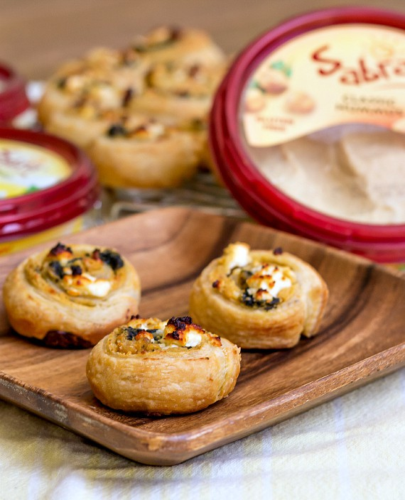 3 puff pastry hummus pinwheels on a wooden plate with containers of Sabra hummus in the background