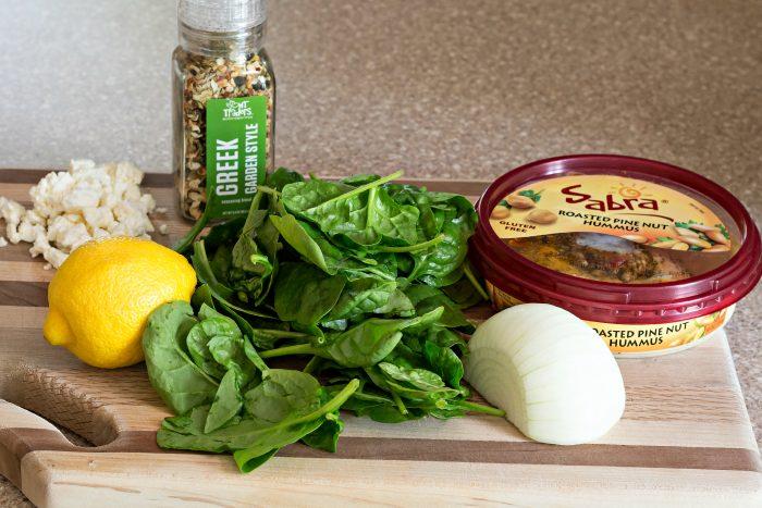 ingredients for hummus pinwheels on a wooden board including hummus, Greek seasoning, fresh spinach, onion, lemon and feta cheese