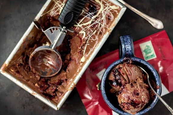 A metal loaf pan of chocolate cherry almond gelato with an ice cream scoop. A single serving of the gelato is to the side.