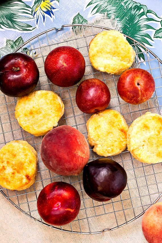 Peaches, plums, and cornmeal biscuits on a cooling rack.