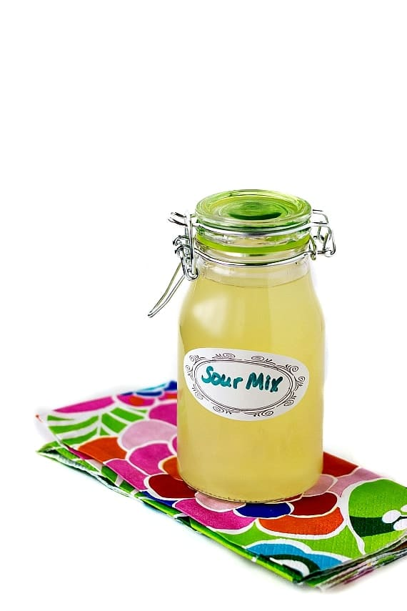 """A sealable bottle of homemade sour mix on a floral napkin. Label on the bottle reads """"Sour Mix""""."""