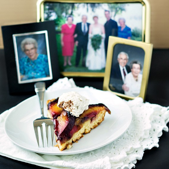 a sliced of kuchen topped with whipped cream on a white plate with family photos in the background