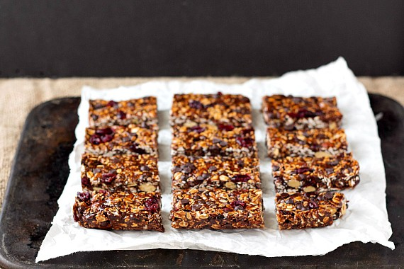 16 sliced vegan chocolate chip granola bars on parchment on a baking stone