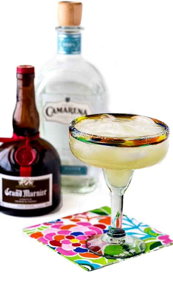 A full margarita glass on a floral napkin with a bottle of Grand Marnier and one of Camarena tequila in the background.