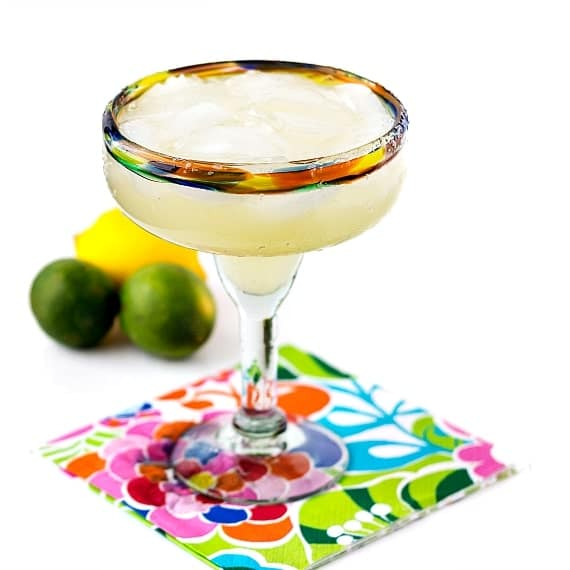 A top shelf margarita with a salted rim on a floral napkin with 2 limes and 1 lemon in the background.