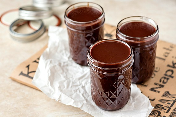 3 glass jars filled with old fashioned hot fudge sauce with canning rings in the background.