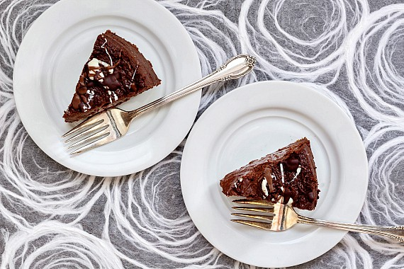 overhead shot of two slices of chocolate cheesecake on white plates with forks