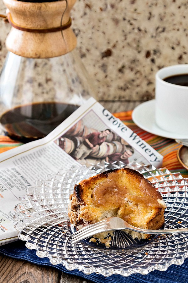 A slice of toasted yeast raised coffee cake on a glass plate along side a newspaper and a carafe of hot coffee.