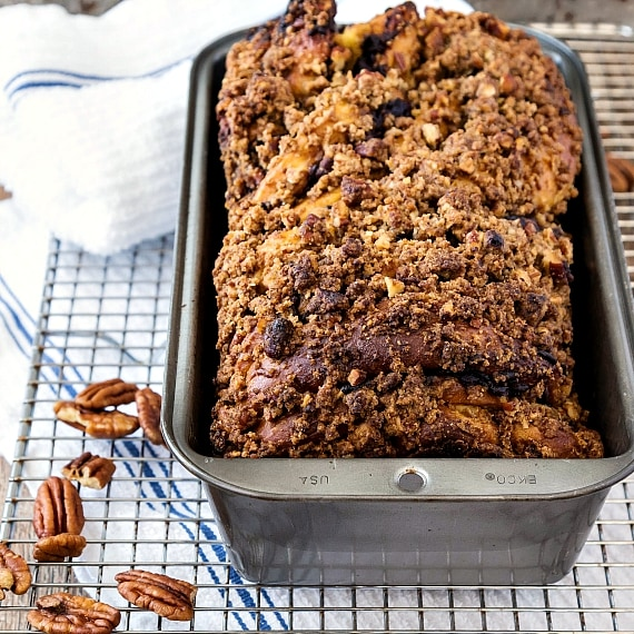 A loaf of sweet bread with streusel topping in a bread pan on a cooling rack with pecans.