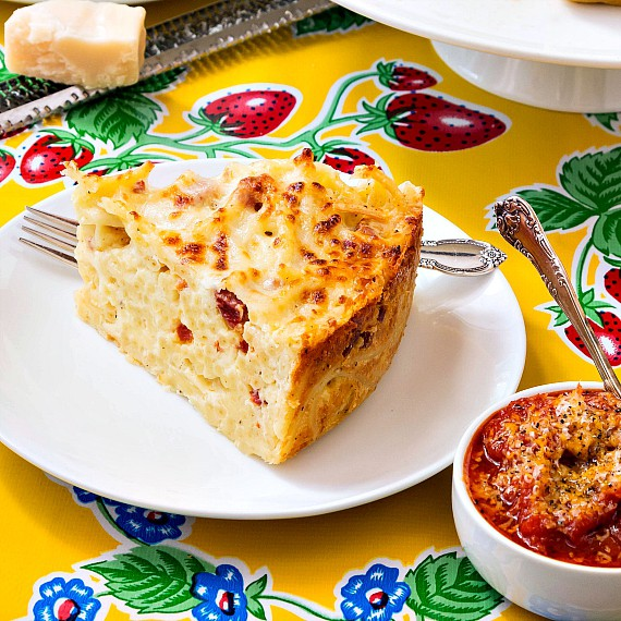 a slice of bucatini pie with a bowl of marinara sauce on a yellow patterned tablecloth