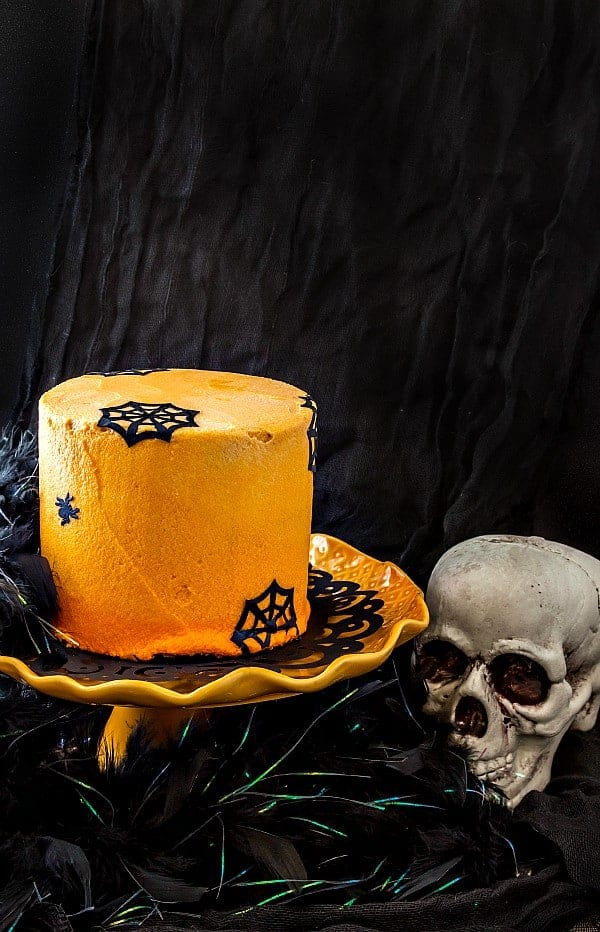 """An orange frosted chocolate Halloween cake decorated with edible """"paper"""" spiders and spider webs."""