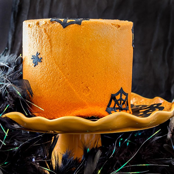A 3 layer chocolate cake frosted with orange frosting and decorated for Halloween.