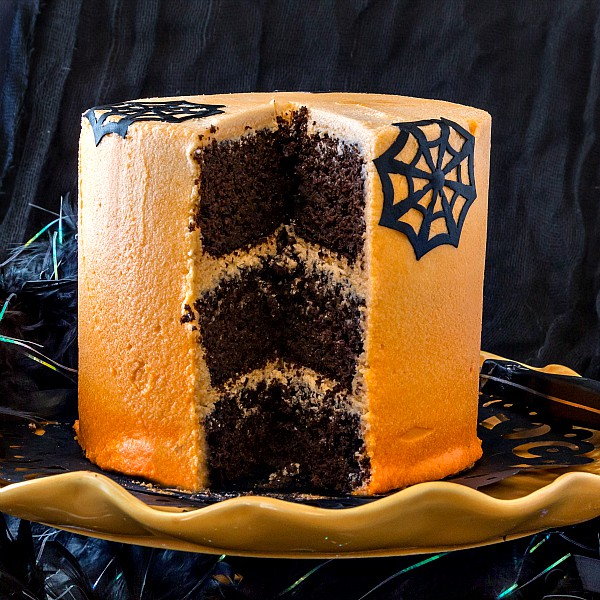 A three layer chocolate Halloween cake with a slice cut out of it, showing chocolate interior.