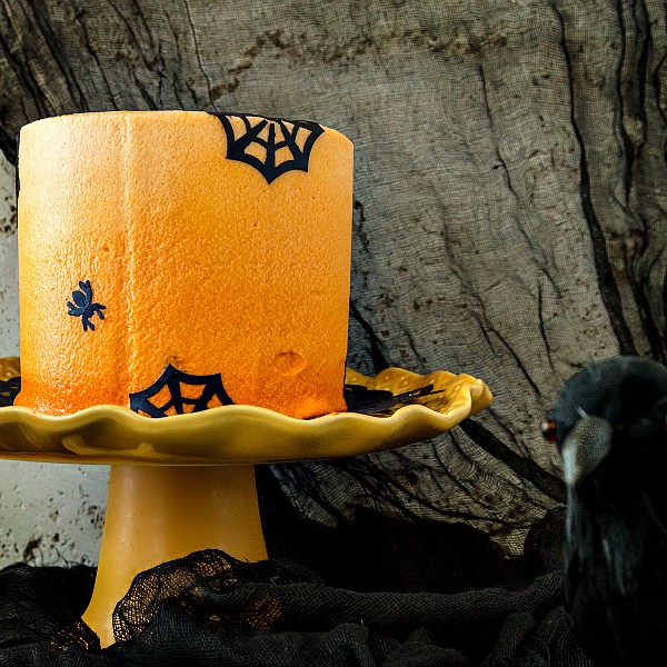 Ombre orange frosted chocolate Halloween cake with black spiders and spiderwebs on it on an orange cake stand.