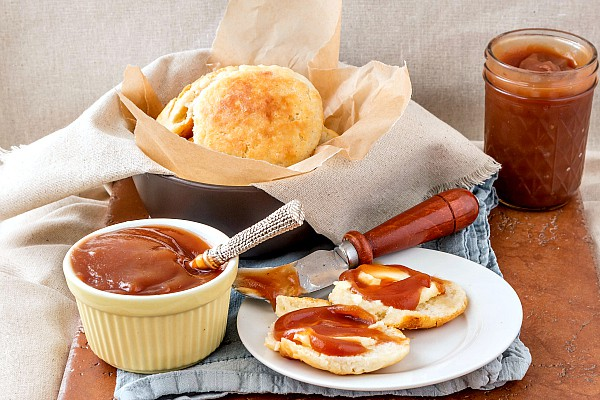 A ramekin of apple butter next to a plate with a split biscuit, slathered with apple butter.