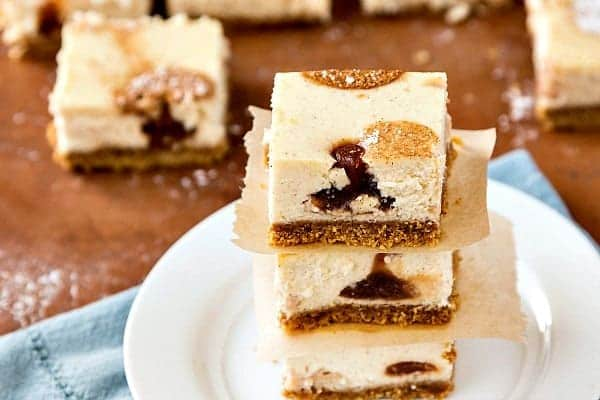 Stack of three cheesecake bars on a white plate with polka dots of apple butter in each.