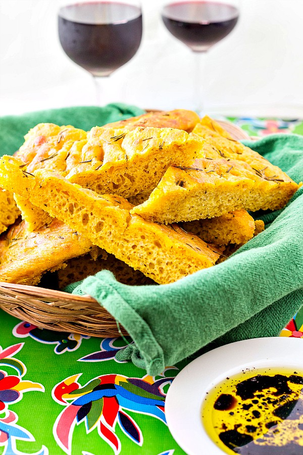 A basket of herbed pumpkin focaccia  cut into triangles with 2 glasses of wine in the background. A dish of dipping oil and vinegar is ready alongside the basket.