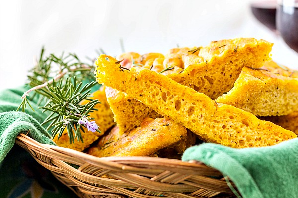 A basket of pieces of focaccia with a rosemary sprig garnish.
