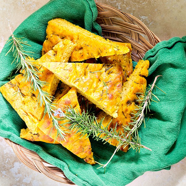 Overhead shot of a basket of pumpkin herb focaccia with rosemary sprigs.