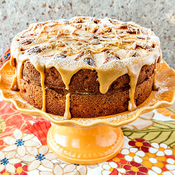 square image of a whole spiced apple cake on an orange cake stand
