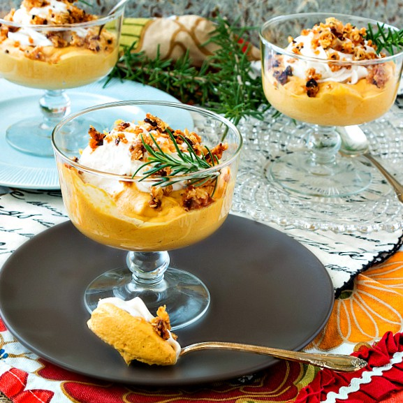 bowls of caramel pumpkin mousse topped with whipped cream, streusel, and sprigs of rosemary
