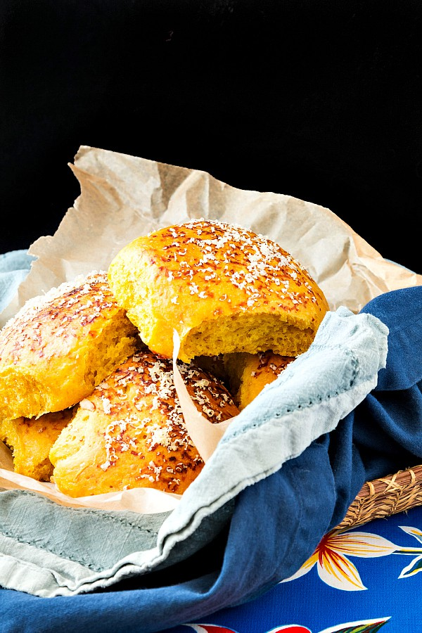 A basket of pumpkin dinner rolls topped with shaved Parmesan cheese.
