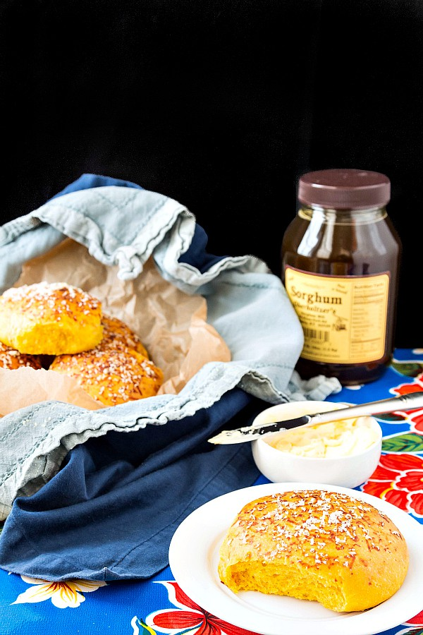 Soft pumpkin dinner rolls in a basket with a bread plate and a small dish of butter and a jar of sorghum syrup.