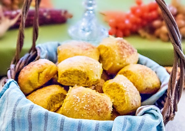 A basket of golden pumpkin dinner rolls on the Thanksgiving table.