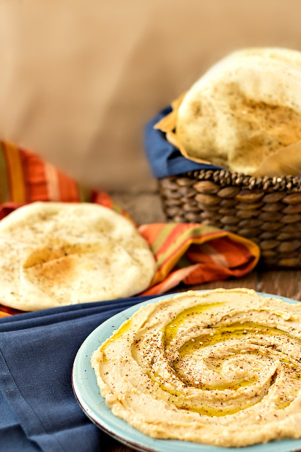 A platter of hummus with oil and spices sprinkled on top. Behind it is a napkin with a piece of torn pita on it. Next to it is a basket of whole wheat pita bread.