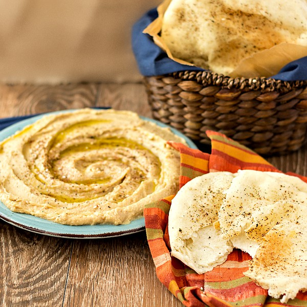 A round dish hummus next to a striped napkin with a torn piece of pita bread. Behind hummus is a basket of pita bread.