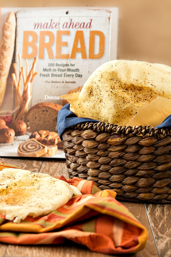 """A basket of whole wheat pita bread, and one serving on a striped napkin. Behind basket is the book, """"Make Ahead Bread. 100 Recipes for Melt-in-Your-Mouth Fresh Bread Every Day."""""""