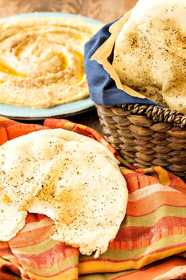 Torn pita bread with a platter of hummus on an orange striped napkin next to a basket of pita bread.